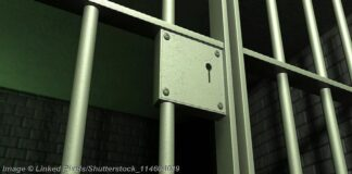 A closeup of the lock of a brick jail cell with iron bars and a door with a locking mechanism - Photo: © Copyright Linked Pixels/Shutterstock