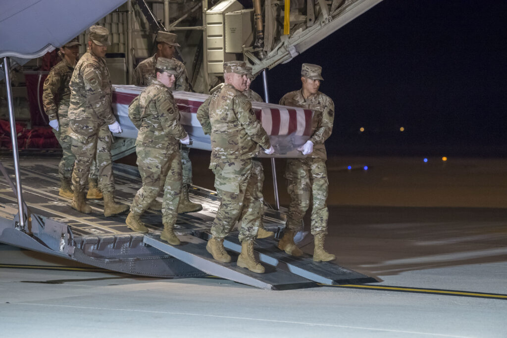 A U.S. Air Force carry team transfers the remains of Ensign Joshua K. Watson, of Coffee, Ala., at Dover Air Force Base, Del., Dec. 8, 2019. Watson was assigned to the Naval Aviation Schools Command, Naval Air Station Pensacola, Fla. (U.S. Air Force Photo by Senior Airman Christopher Quail)