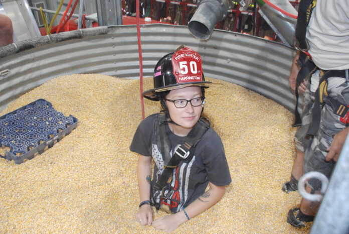 Volunteer firefighter Makayla Parson helped demonstrate how the grain bin rescue tube works last year at the Harrington Fire Department after they received the award from Nationwide.